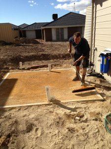 Guy raking the base for a new rainwater tank