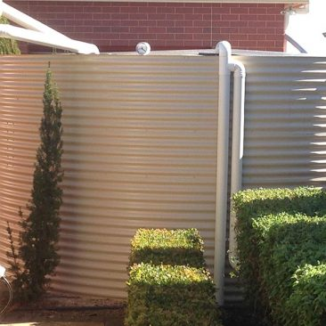Cream Aquaplate tank with green hedge in foreground