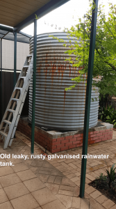 galvanised rainwater tank with ladder next to it.