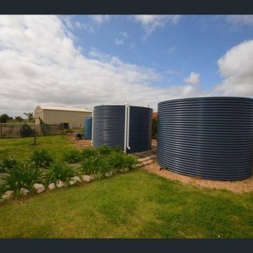2 rainwater tanks deep ocean colour side by side in rural setting