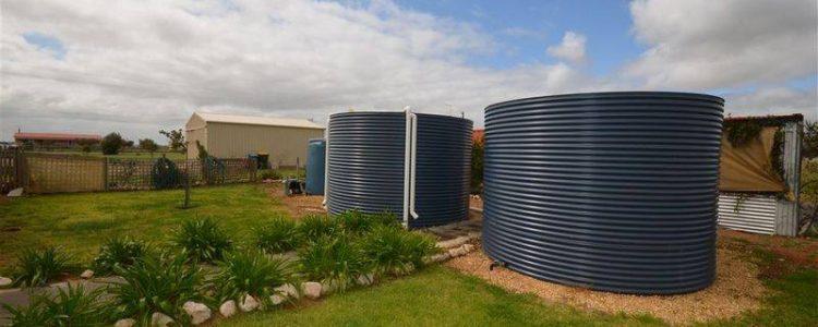 2 rainwater tanks deep ocean colour side by side in rural setting