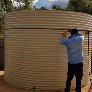 Steve completing a rainwater tank using a tool to join the sections together