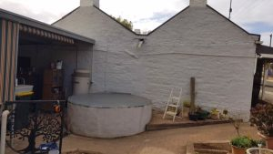 White base for rainwater tank on side of cottage in Kapunda SA
