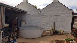 White base for rainwater tank on side of cottage in Kapunda SA