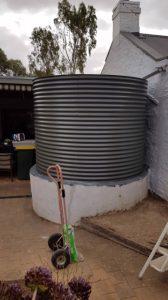 steel grey rainwater tank on white base at cottage in Kapunda SA