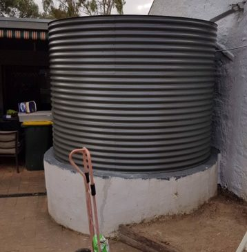 steel grey rainwater tank on white base at cottage in Kapunda SA