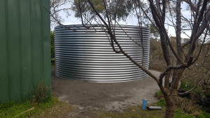 Completed Galvanised rainwater tank next to green shed with tree in foreground