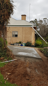 concrete base for rainwater tank with cream house in background