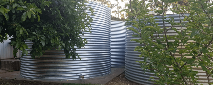 view of completed galvanised rainwater tanks amongst the trees